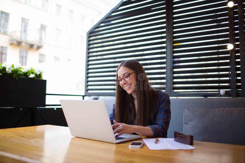 Empresaria feliz joven que tiene conferencia en línea sobre el ordenador portátil durante resto en restaurante foto de archivo