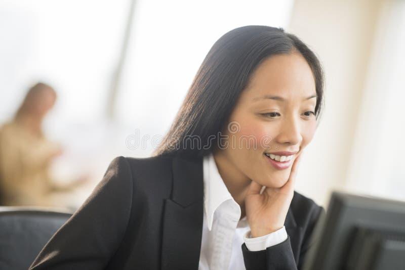 Empresaria feliz Looking At Computer en oficina imágenes de archivo libres de regalías
