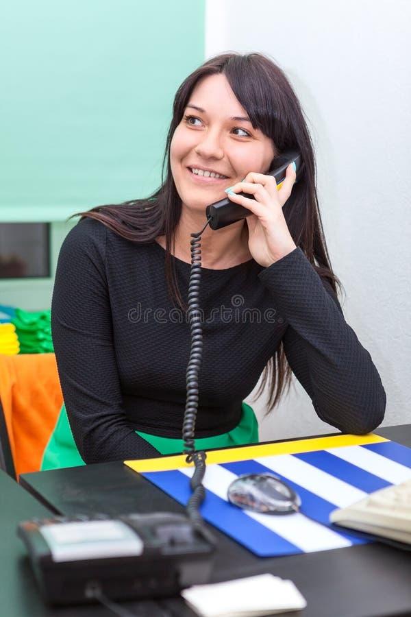 Empresaria feliz que habla en el teléfono en oficina fotos de archivo