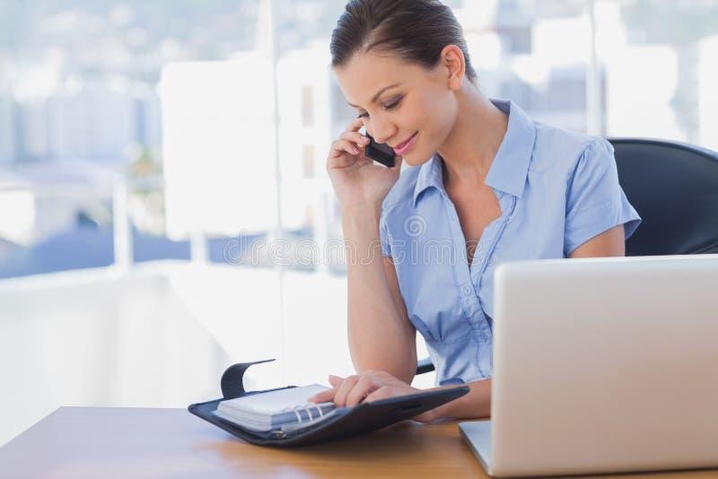 Empresaria feliz que llama con su teléfono móvil y que mira imagen de archivo
