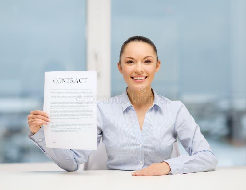 Empresaria feliz que lleva a cabo el contrato en oficina fotografía de archivo