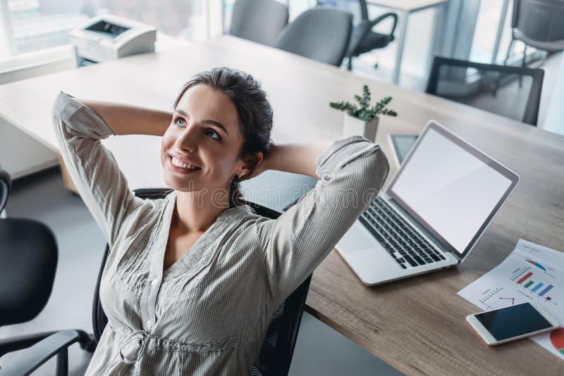 Empresaria feliz que se relaja con las manos detrás de la cabeza en el escritorio de oficina Concepto que sueña despierto fotos de archivo libres de regalías