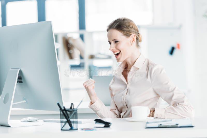 Empresaria feliz que se sienta cerca del ordenador moderno en la oficina foto de archivo libre de regalías