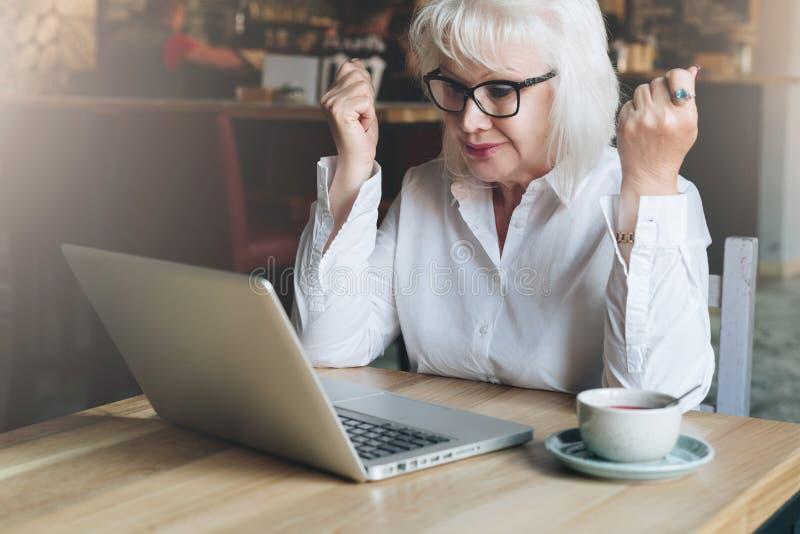 Empresaria feliz que se sienta en café en la tabla delante del ordenador portátil, llevando a cabo las manos ascendentes y mirand imagen de archivo