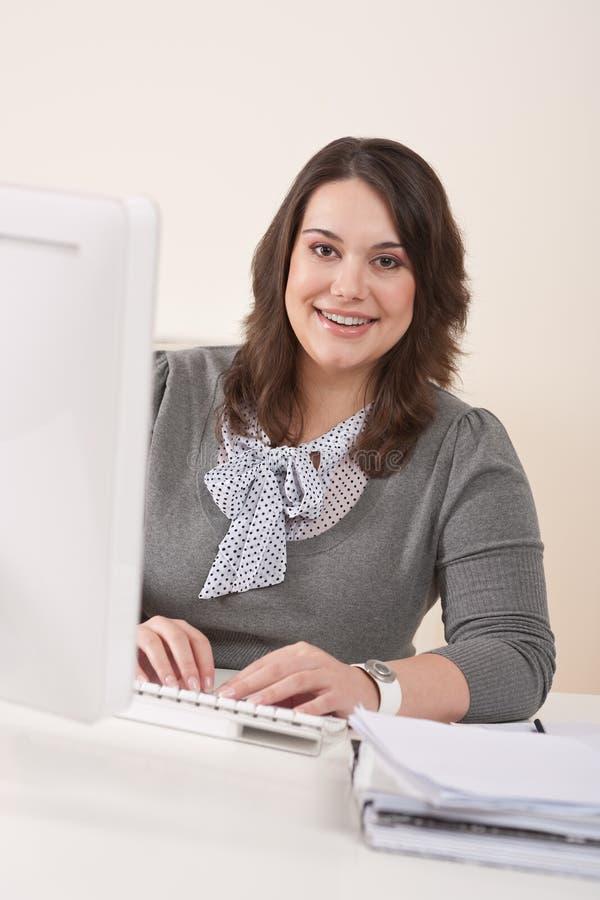 Empresaria feliz que se sienta en el escritorio de oficina foto de archivo