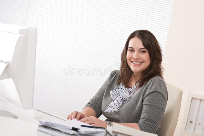 Empresaria feliz que se sienta en el escritorio de oficina imagenes de archivo
