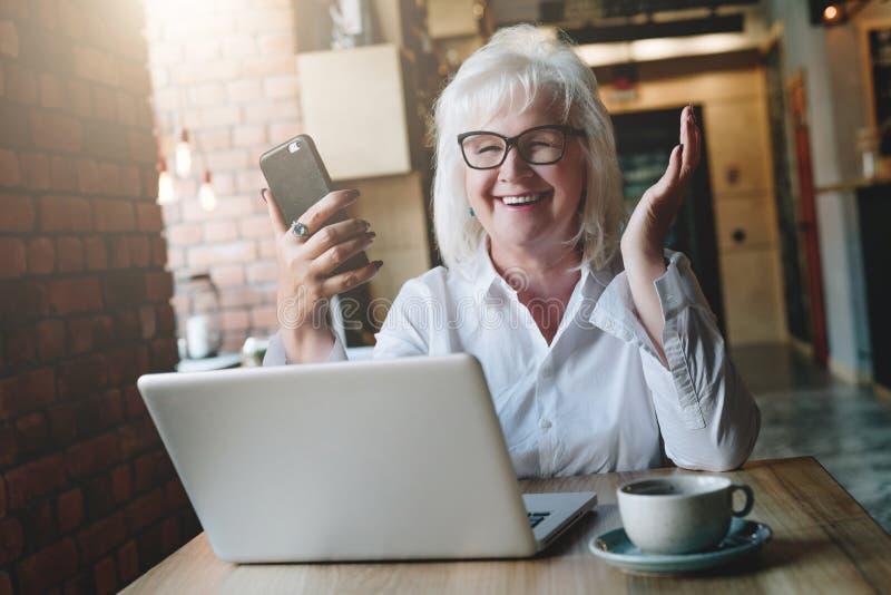 Empresaria feliz que se sienta en la tabla delante del ordenador portátil, sosteniéndose fotos de archivo libres de regalías