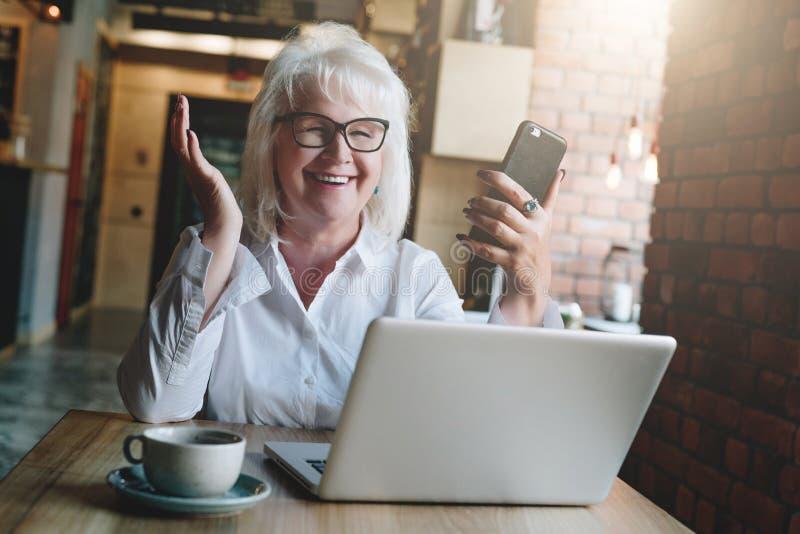 Empresaria feliz que se sienta en la tabla delante del ordenador portátil, sosteniéndose foto de archivo libre de regalías