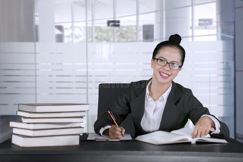 Empresaria feliz que trabaja demasiado en la oficina imagen de archivo