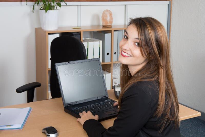 empresaria feliz que usa el ordenador mientras que se sienta en el escritorio en la oficina foto de archivo libre de regalías