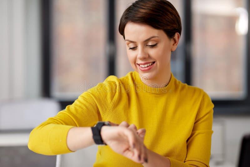 Empresaria feliz que usa el reloj elegante en la oficina imagenes de archivo