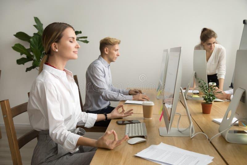 Empresaria feliz tranquila que medita en el escritorio de oficina que trabaja con fotografía de archivo libre de regalías