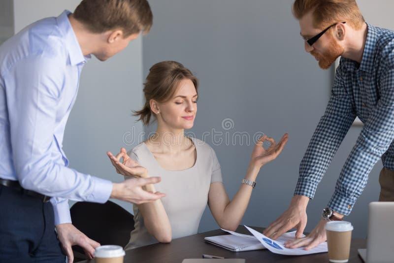 Empresaria feliz tranquila que medita en la oficina que no escucha c foto de archivo libre de regalías