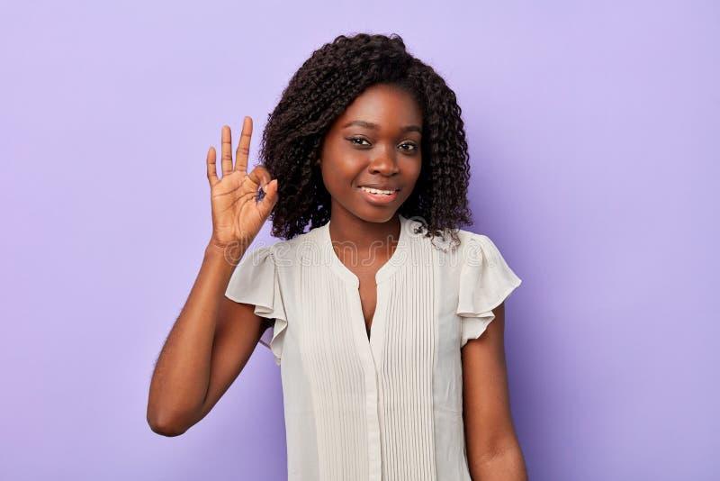 Empresaria femenina afro bonita sonriente que hace la muestra de la autorización imagen de archivo