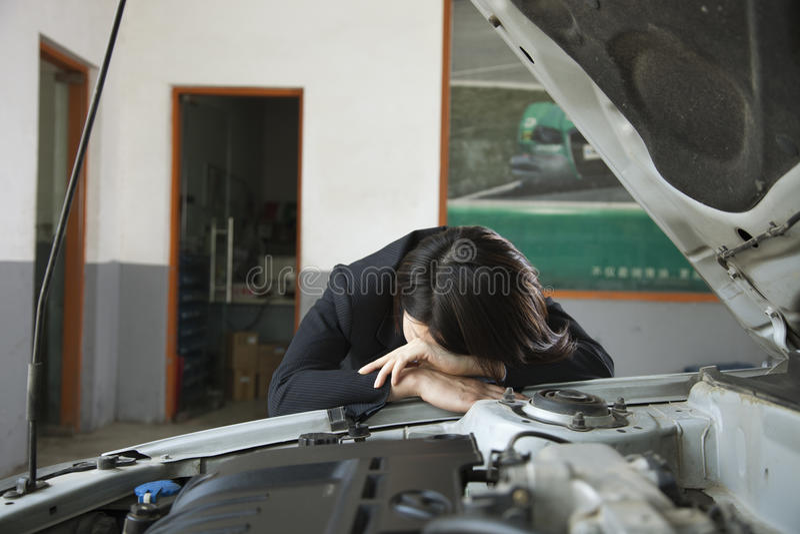 Empresaria Frustrated con el coche, cabeza en el lado del coche imagenes de archivo