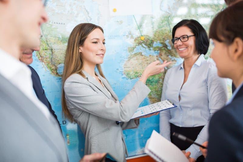 Empresaria Gesturing While Discussing con los colegas por el mapa del mundo fotos de archivo libres de regalías