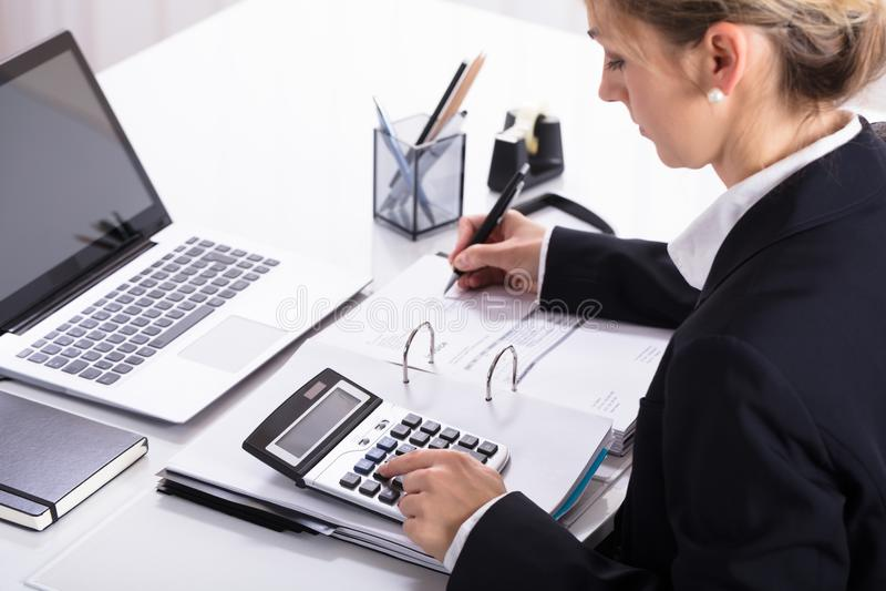 Empresaria Hand Calculating Invoice que usa la calculadora fotografía de archivo libre de regalías