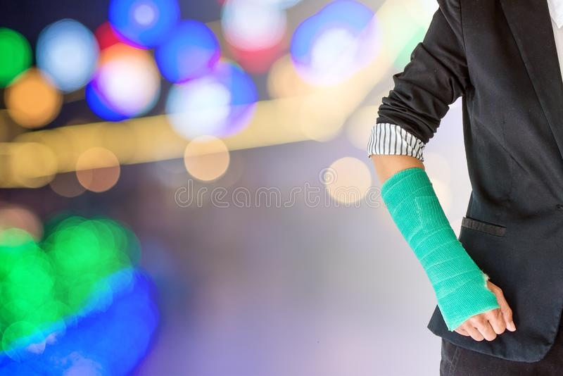 Empresaria herida con el verde echado a mano y brazo en la luz b imágenes de archivo libres de regalías