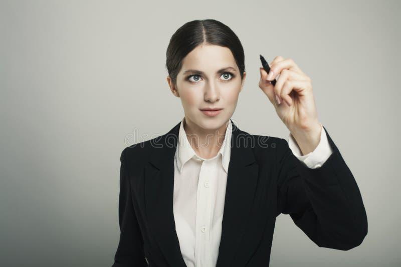 Empresaria hermosa joven con la escritura de la pluma en la pantalla fotografía de archivo