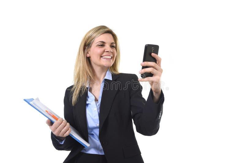 Empresaria hermosa joven del pelo rubio que usa Internet app en el teléfono móvil que celebra la sonrisa de la carpeta y de la pl imagen de archivo