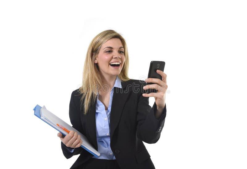 Empresaria hermosa joven del pelo rubio que usa Internet app en el teléfono móvil que celebra la sonrisa de la carpeta y de la pl imagenes de archivo