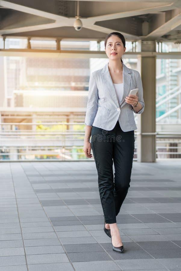 Empresaria hermosa joven que camina afuera imagen de archivo