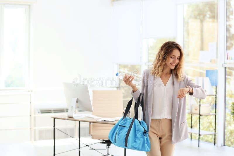 Empresaria hermosa joven que sostiene el bolso de la aptitud en oficina imagen de archivo