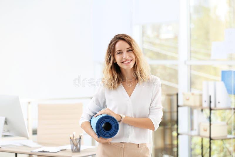 Empresaria hermosa joven que sostiene la estera de la yoga en oficina fotos de archivo