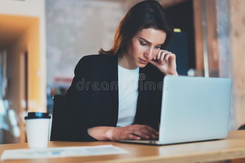 Empresaria hermosa joven que usa el ordenador portátil en la oficina moderna Fondo enmascarado horizontal foto de archivo
