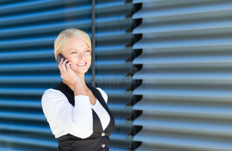 Empresaria hermosa que arregla una reunión por el teléfono fotografía de archivo