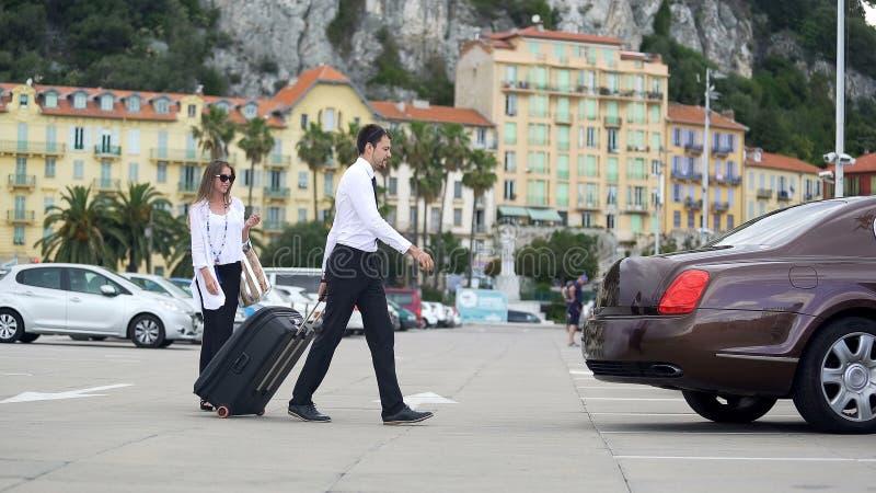 Empresaria hermosa que camina para llevar en taxi con el chauffer, servicios de lujo del coche imagen de archivo libre de regalías