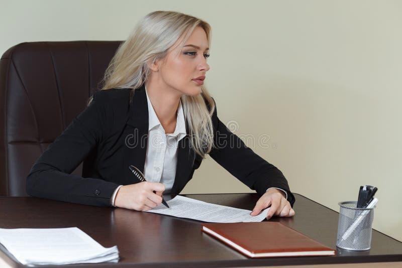 Empresaria hermosa que firma un contrato o un documento en un escritorio en la oficina fotografía de archivo libre de regalías