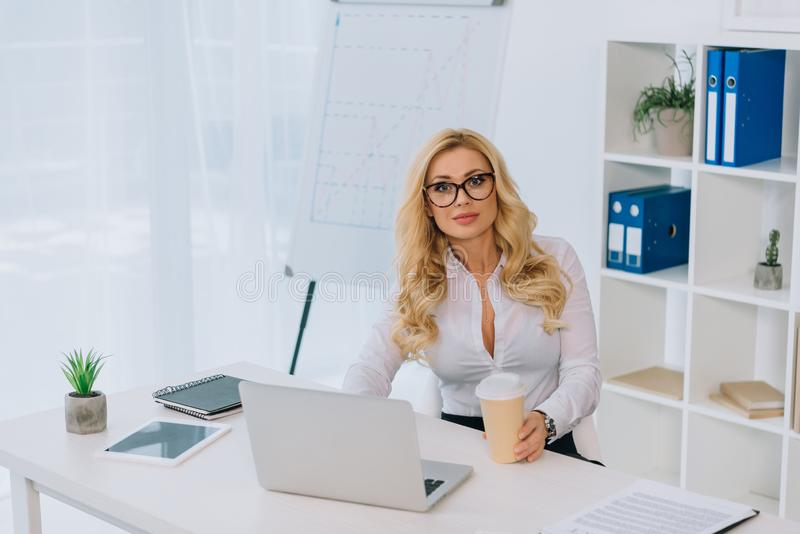 empresaria hermosa que se sienta en la tabla con el ordenador portátil y que se considera disponible imagen de archivo