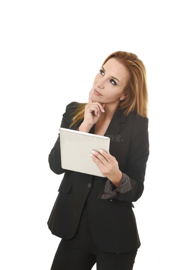Empresaria hermosa rubia que sostiene el traje de negocios que lleva del cojín digital de la tableta que parece pensativo fotos de archivo