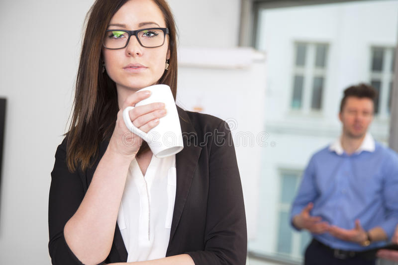 Empresaria Holding Coffee Mug mientras que colega que se coloca en el CCB foto de archivo libre de regalías