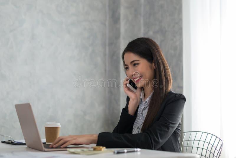 Empresaria joven asiática hermosa que trabaja en el ordenador portátil mientras que sea s fotos de archivo