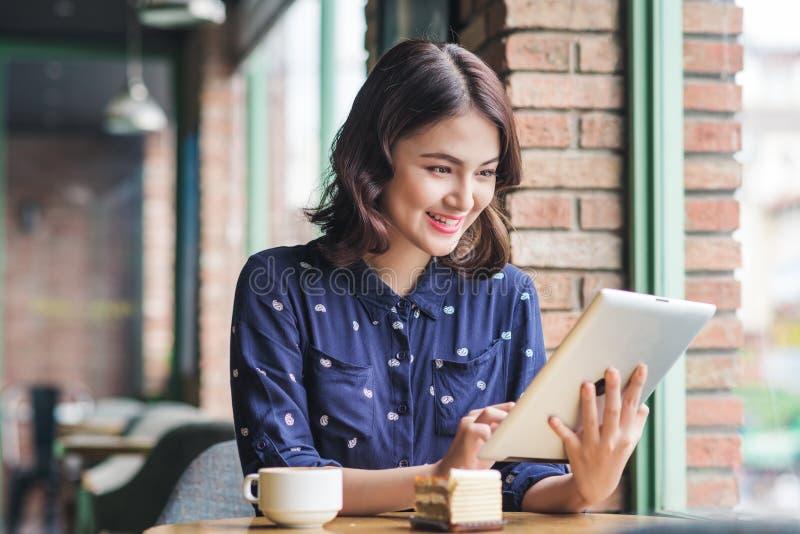 Empresaria joven asiática linda hermosa en el café, usando digi foto de archivo