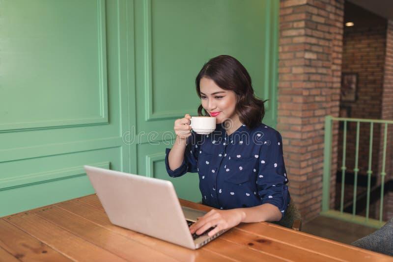 Empresaria joven asiática linda hermosa en el café, usando lapt fotos de archivo