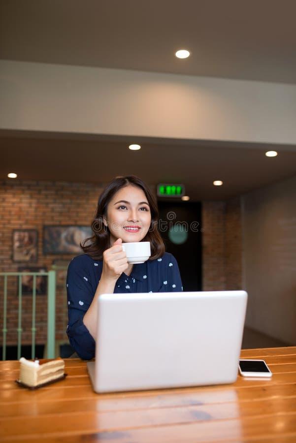 Empresaria joven asiática linda hermosa en el café, usando lapt fotografía de archivo
