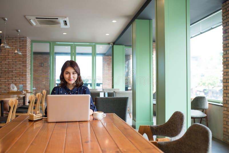 Empresaria joven asiática linda hermosa en el café, usando lapt foto de archivo libre de regalías