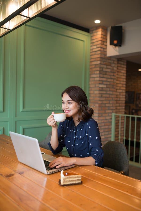 Empresaria joven asiática linda hermosa en el café, usando lapt fotos de archivo libres de regalías