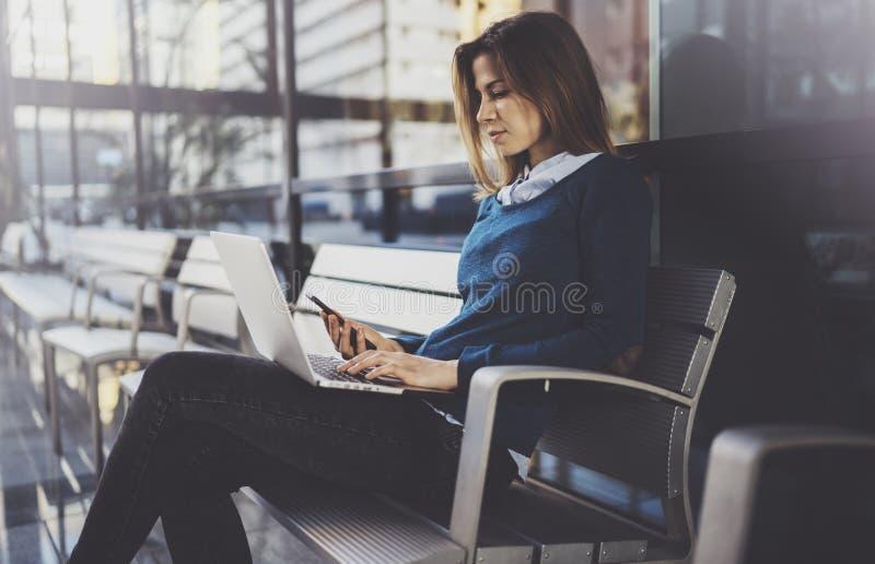 Empresaria joven atractiva que lleva la ropa casual y que trabaja en el centro de la oficina de negocios Hembra que usa al contem foto de archivo