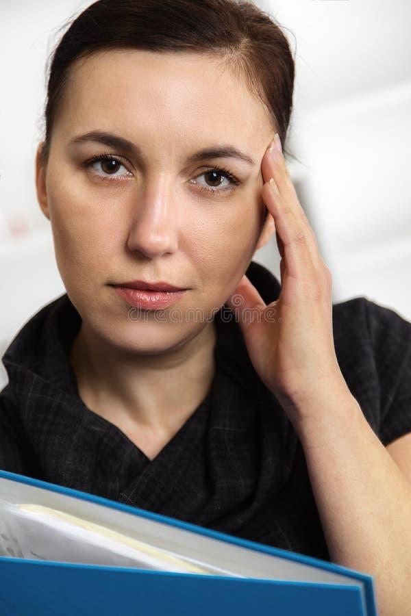 Empresaria joven atractiva que se coloca en la oficina foto de archivo libre de regalías