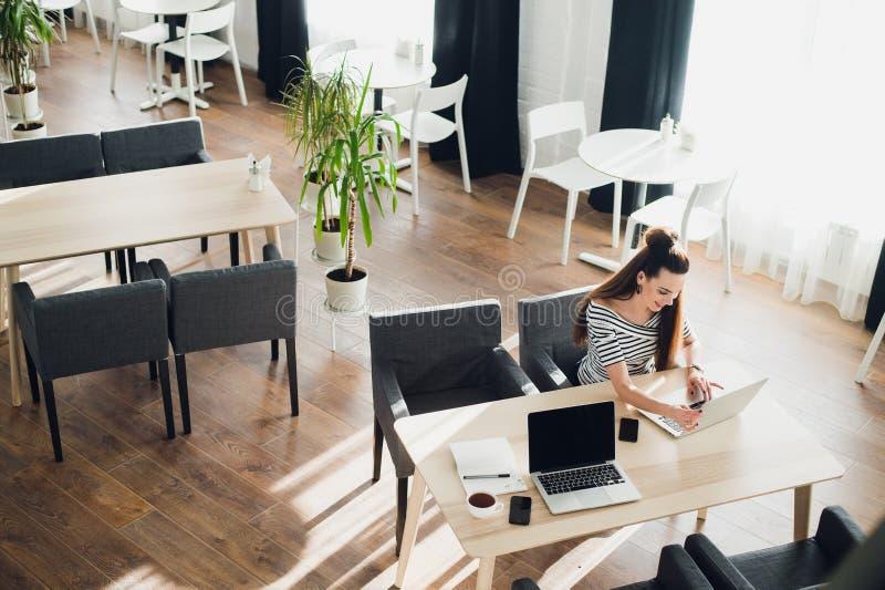 Empresaria joven atractiva que trabaja en el ordenador portátil que se sienta en la barra imagenes de archivo
