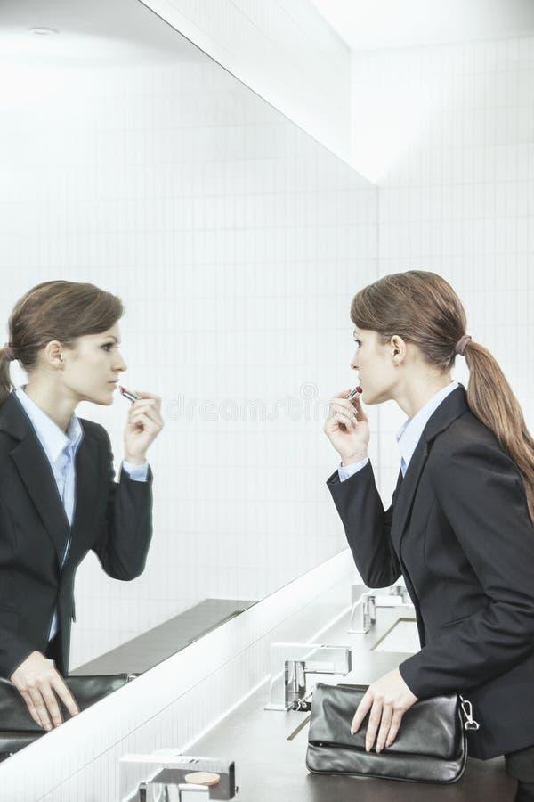 Empresaria joven con el pelo largo que mira en el espejo y que pone en el lápiz labial en el cuarto de baño foto de archivo libre de regalías