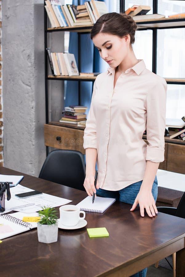 Empresaria joven con la pluma que se coloca en la tabla y que escribe en cuaderno imagenes de archivo