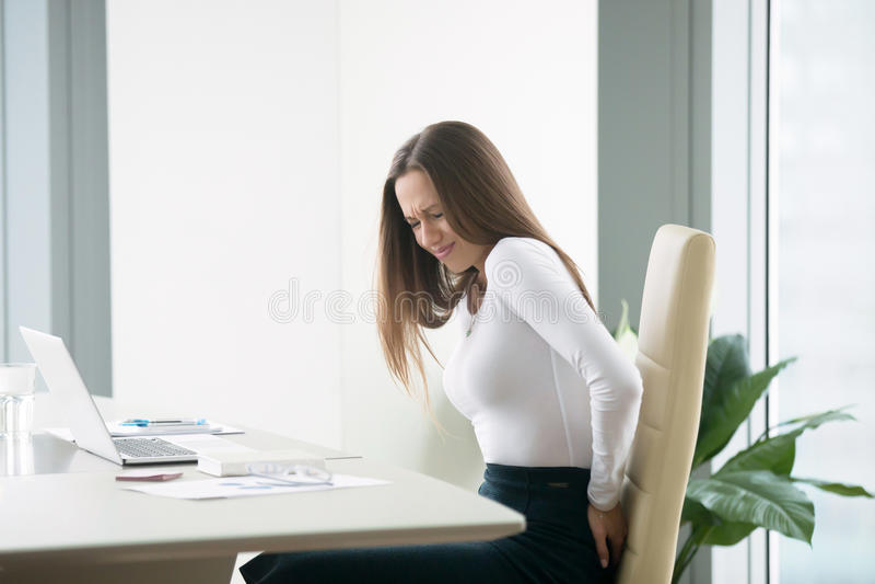 Empresaria joven con un backpain imagen de archivo libre de regalías
