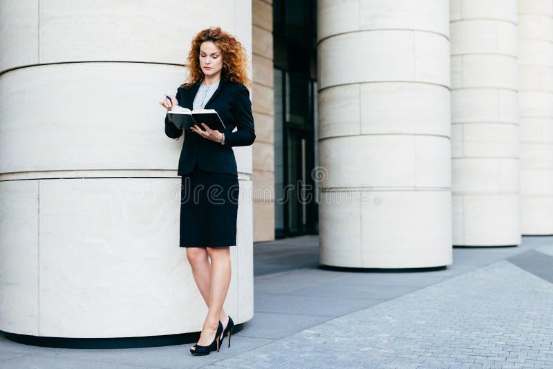 Empresaria joven delgada en ropa elegante y zapatos de tacón alto, concentrando mirada en su cuaderno, encontrando la fecha de re foto de archivo libre de regalías