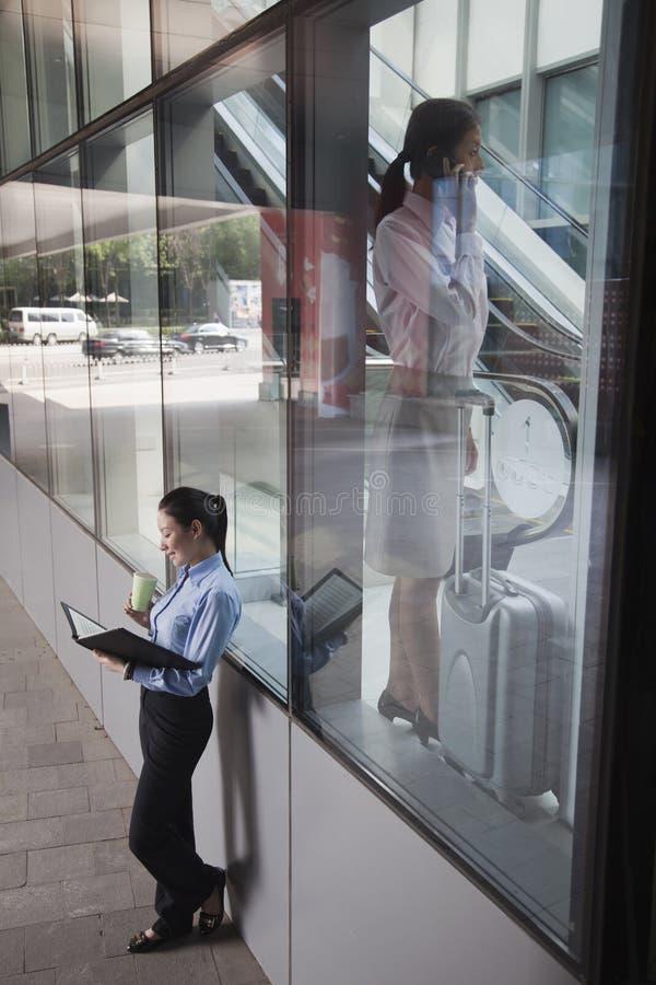 Empresaria joven dentro del edificio que habla en el teléfono, otras mujeres fuera del edificio que mira sus notas imagen de archivo
