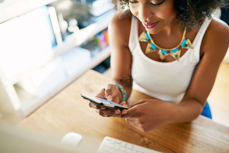 Empresaria joven elegante que comprueba su móvil fotos de archivo libres de regalías